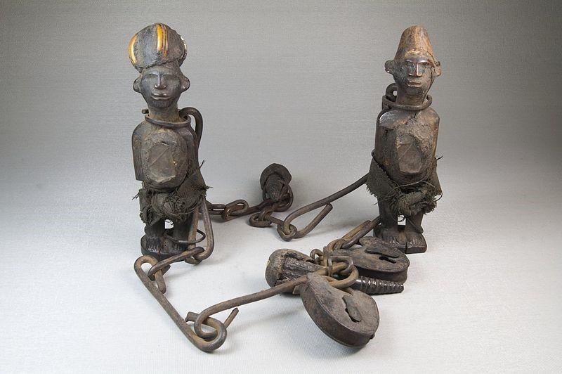 Fotografia de dois nkisi feitos de madeira com detalhes em metal.