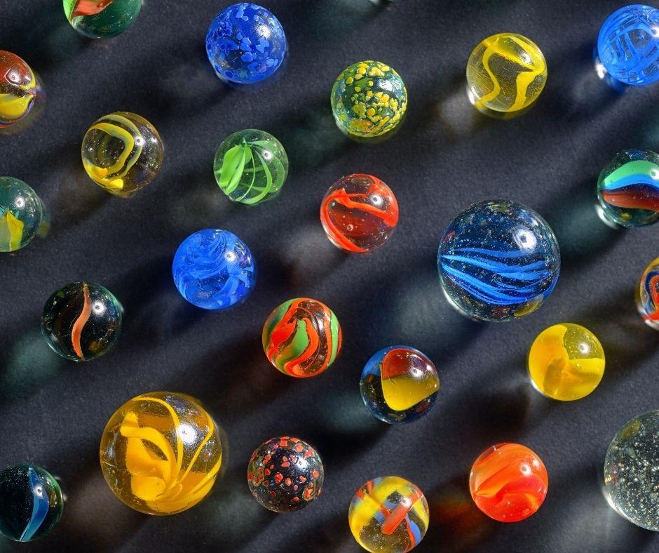 Várias bolinhas de gude de diferentes tamanhos. Fonte da imagem: Getty Images.
