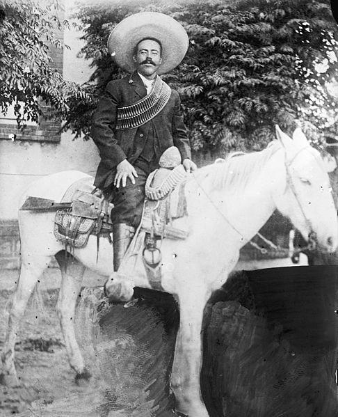 Foto de Pancho Villa montado em um cavalo branco com uma arma na cela.