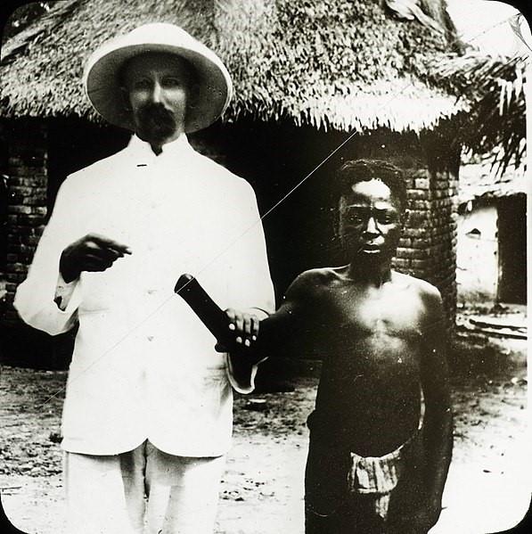 Colonizador branco vestindo roupas brancas e um chapéu de aba redonda apontando para o braço decepado de um menino negro, que está sem camisa e com uma expressão de sofrimento. imperialismo na África