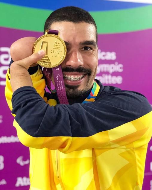 A imagem mostra o atleta Daniel Dias mostrando uma de suas medalhas de ouro sobre o rosto, com um grande sorriso.