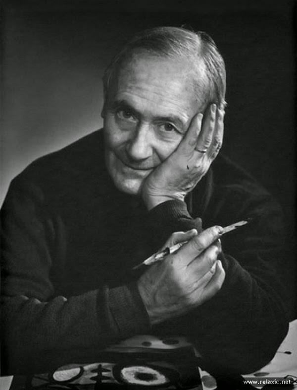 Retrato de Joan Miró, segurando sua cabeça com uma mão e um pincel com a outra. A frente de um de seus trabalhos. Miró foi um dos mais reconhecidos artistas plásticos da Espanha.